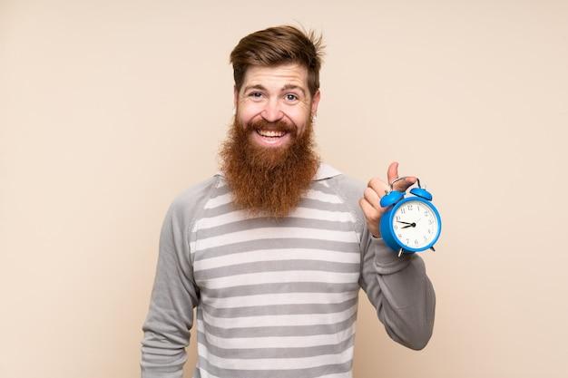 Homme rousse avec une longue barbe tenant un réveil vintage
