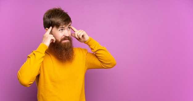 Homme rousse avec longue barbe sur violet isolé ayant des doutes et de la pensée
