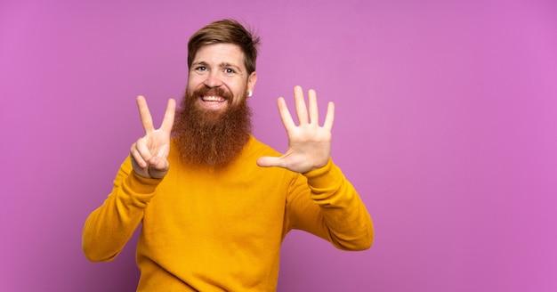 Homme rousse avec longue barbe sur violet isolé comptant sept avec les doigts
