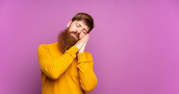 Homme rousse avec longue barbe sur violet isolé faisant un geste de sommeil dans une expression adorable