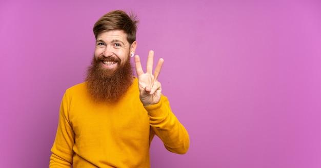 Homme rousse avec une longue barbe sur violet isolé heureux et en comptant trois avec les doigts