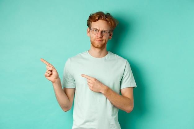 Homme rousse à lunettes grimaçant, fronçant les sourcils déçu et pointant vers la gauche, montrant une mauvaise offre promotionnelle, debout sur fond turquoise.