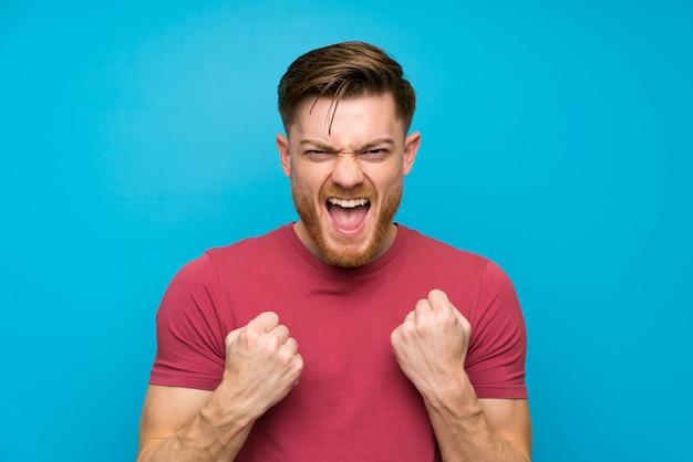 Homme rousse sur un mur bleu isolé célébrant une victoire