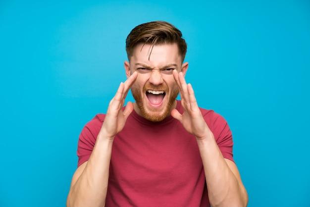 Homme rousse sur un mur bleu isolé, criant avec la bouche grande ouverte
