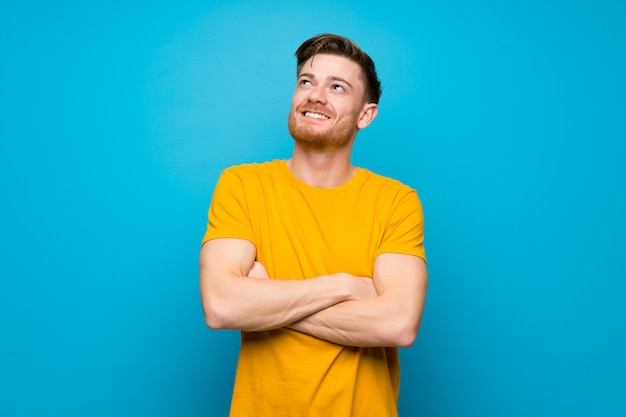 Homme rousse sur mur bleu, levant en souriant