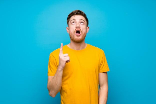 Homme rousse sur un mur bleu pointant vers le haut et surpris