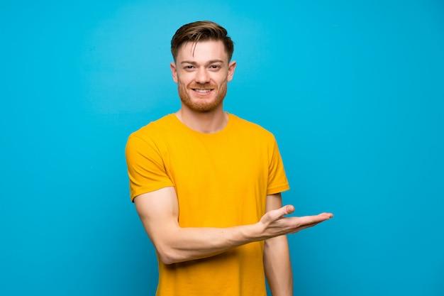 Homme rousse sur un mur bleu présentant une idée tout en regardant en souriant