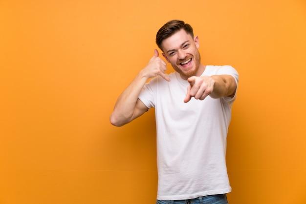 Homme rousse sur un mur brun faisant un geste de téléphone et pointant le devant