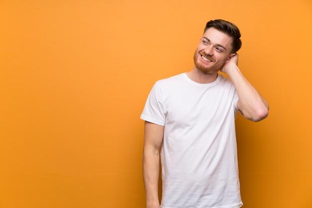 Homme rousse sur mur brun, pensant une idée