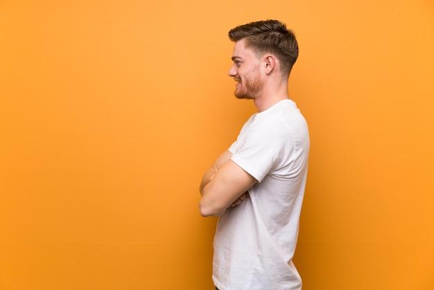 Homme rousse sur mur brun en position latérale