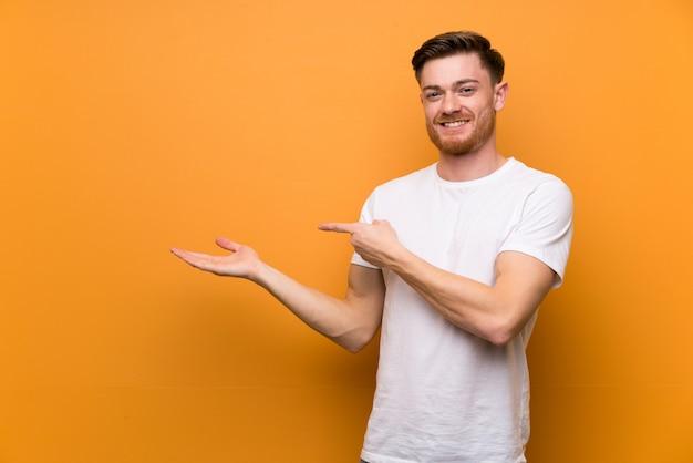 Homme rousse sur un mur brun tenant une surface imaginaire sur la paume pour insérer une annonce