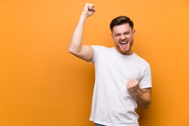 Homme rousse sur un mur marron célébrant une victoire