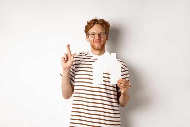 Homme rousse plein d'espoir rêvant d'acheter une maison, tenant du papier à la maison et croiser les doigts pour la bonne chance, faire un vœu, debout sur fond blanc.