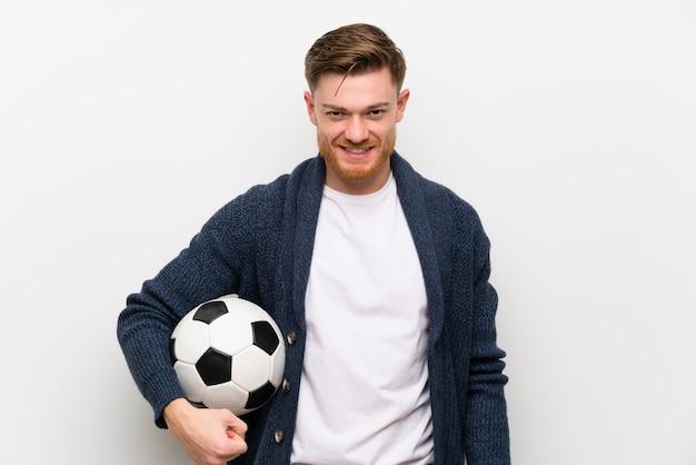 Homme rousse tenant un ballon de foot