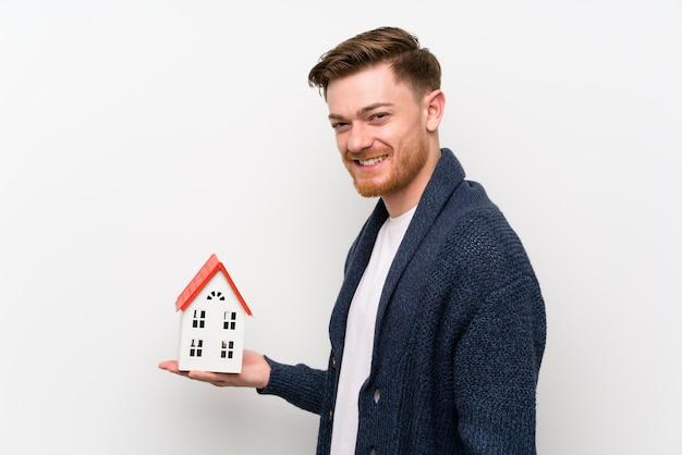 Homme rousse tenant une petite maison
