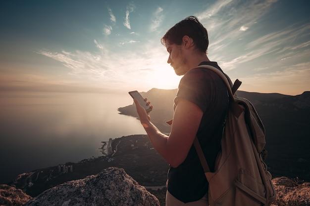 Homme routard utilisant un smartphone relaxant au sommet d'une montagne voyageant seul. mode de vie vacances actives technologie moderne concept de millénaires. merveilleuse aube. maquette de texte.