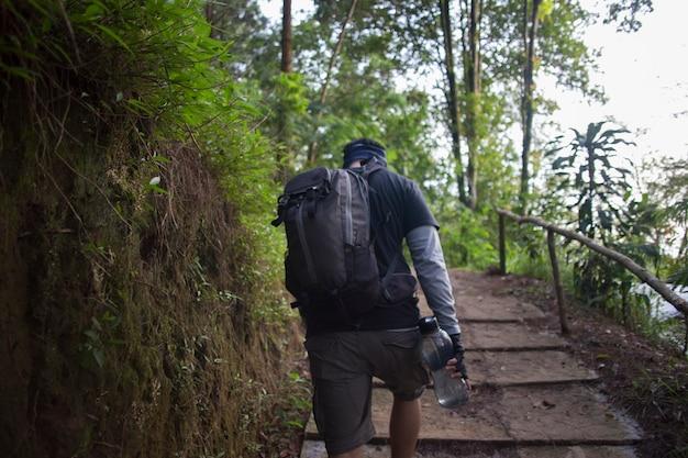 Un homme routard voyage seul, avec un sac à dos dans les montagnes