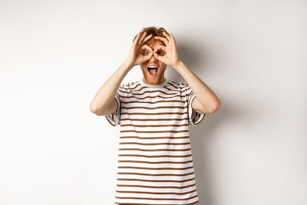 Homme roux impressionné vérifiant l'offre promotionnelle, regardant la caméra avec des jumelles à main, souriant étonné, fond blanc