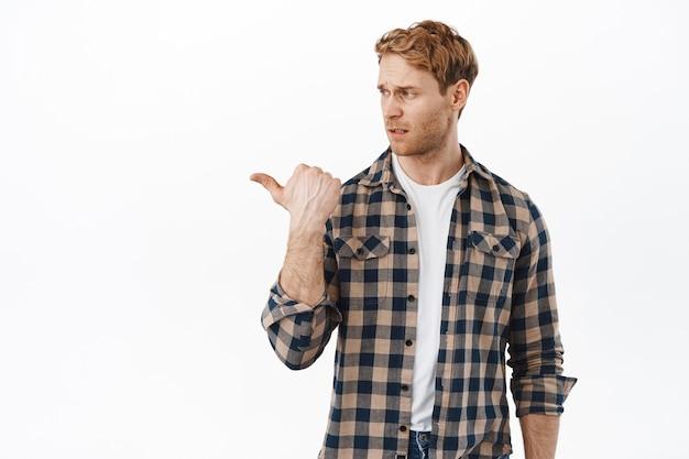 Un homme roux sceptique grince des dents de quelque chose de mal, regardant et pointant vers la gauche avec un regard déçu, ayant des doutes, debout sur un mur blanc