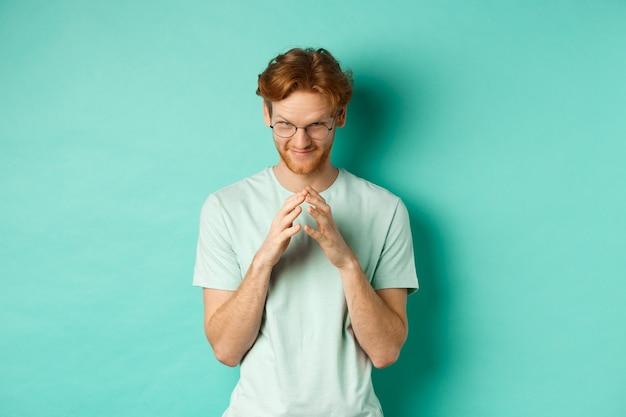 Homme roux sournois dans des lunettes et un t-shirt lançant une idée, des doigts de clocher et un regard sous le front avec un sourire narquois et suffisant, debout sur un fond de menthe.