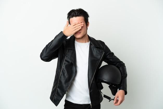 Homme russe avec un casque de moto isolé sur fond blanc couvrant les yeux à la main. je ne veux pas voir quelque chose