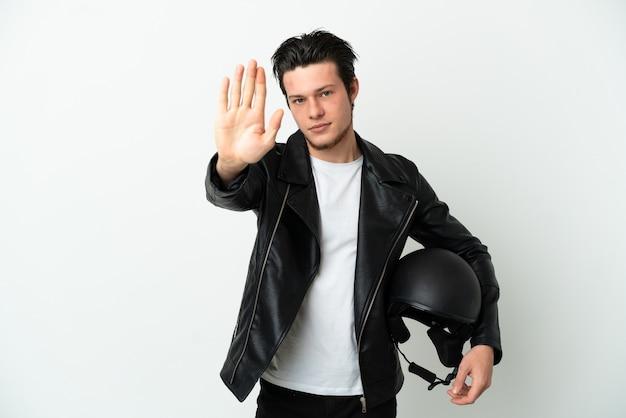 Homme russe avec un casque de moto isolé sur fond blanc faisant un geste d'arrêt