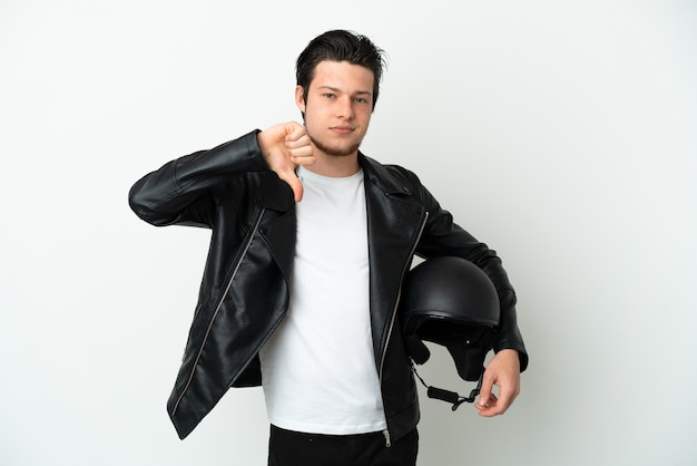Homme russe avec un casque de moto isolé sur fond blanc montrant le pouce vers le bas avec une expression négative