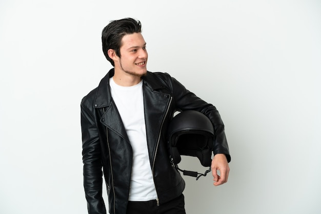 Homme russe avec un casque de moto isolé sur fond blanc regardant sur le côté et souriant