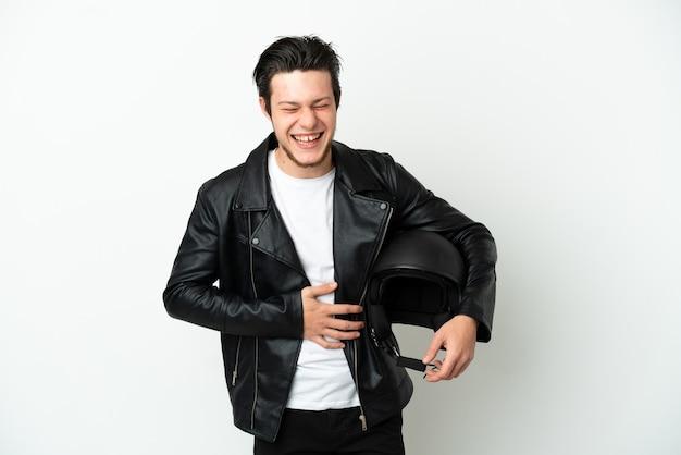 Homme russe avec un casque de moto isolé sur fond blanc souriant beaucoup