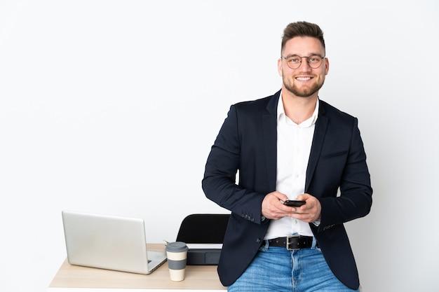 Homme russe dans un bureau sur un mur blanc en envoyant un message avec le mobile
