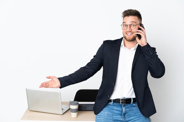 Homme russe dans un bureau sur un mur blanc en gardant une conversation avec le téléphone mobile avec quelqu'un