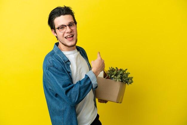Homme russe faisant un mouvement tout en ramassant une boîte pleine de choses isolées sur fond jaune pointant vers l'arrière