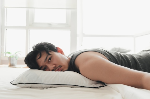 L'homme s'allonge sur un lit blanc confortable alors qu'il est épuisé.