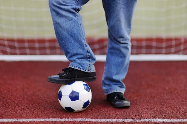 Homme s'amusant à jouer à un match de foot / football le jour d'été
