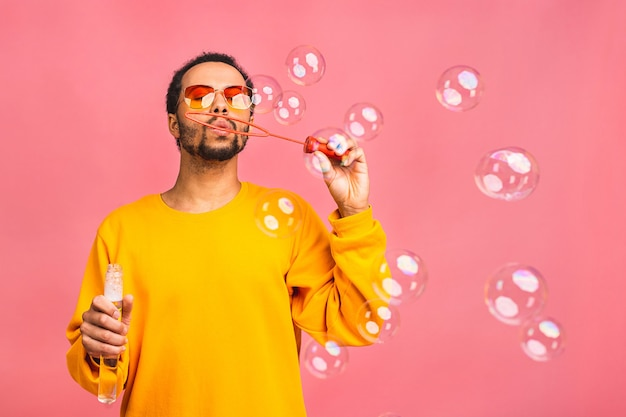 L'homme s'amuse avec des bulles de savon. isolé sur rose