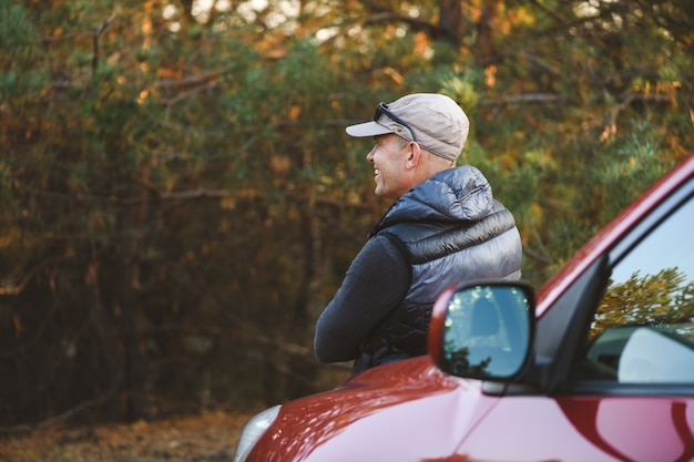 Un homme s'appuie sur le capot d'une voiture