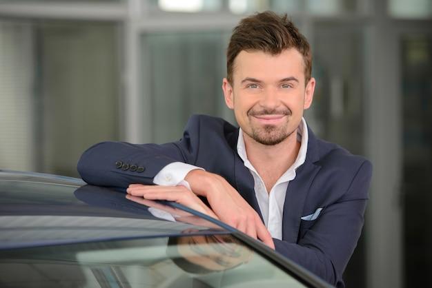 L'homme s'appuya sur la voiture et sourit à la caméra.