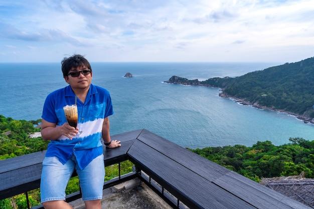 Un homme s'assoit au point de vue supérieur en regardant la côte de la mer tenant un café au lait, un homme asiatique se détend avec un café et une vue sur l'océan