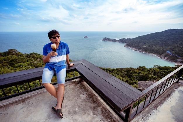 Un homme s'assoit sur une chaise de terrasse en bois au point de vue supérieur tenant un café au lait glacé, un homme asiatique se détend avec un café et une vue sur l'océan