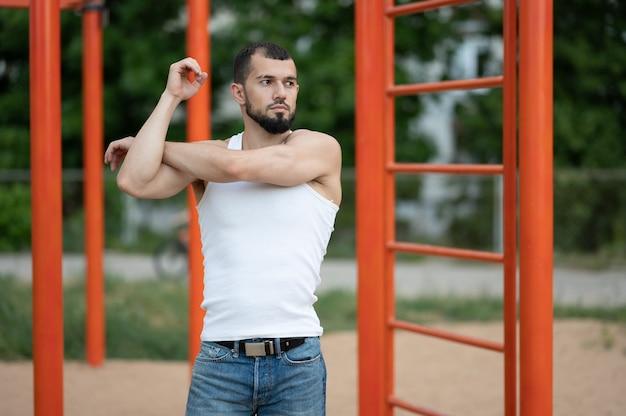 Un homme s'échauffe avant de s'entraîner dans la rue. entraînement, entraînement, style de vie