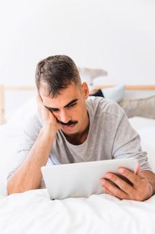 Homme s'ennuie en regardant un film sur une tablette