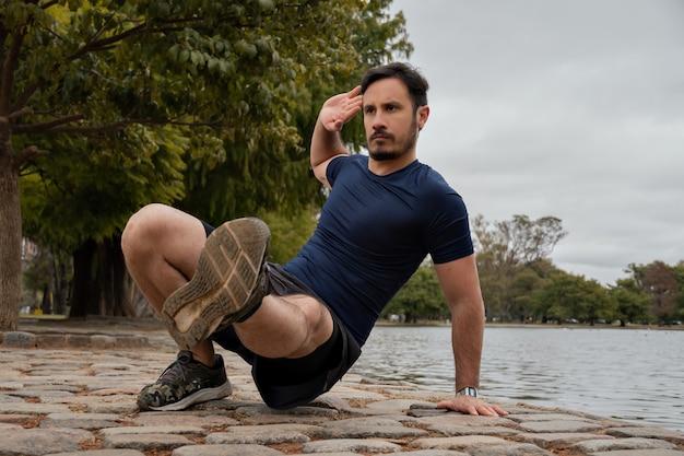 Un homme s'entraîne dans le parc, ne s'appuyant que sur un pied et la main opposée