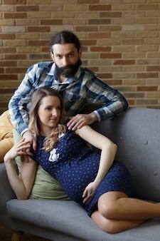 Un homme et sa femme enceinte posent sur un canapé à la maison