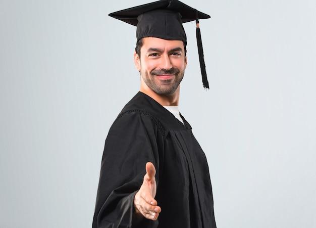 Homme sur sa journée de remise des diplômes université de poignée de main après une bonne affaire sur fond gris