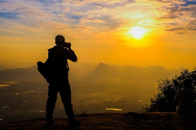 Homme avec sa silhouette de caméra reflex numérique sur fond de coucher de soleil