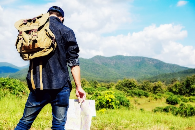 Homme avec un sac à bagages à la campagne