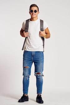 Un homme avec un sac à dos sur le dos en jeans tshirt baskets et lunettes sur son visage