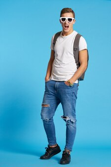 Un homme avec un sac à dos à lunettes et en jeans baskets tshirt bleu