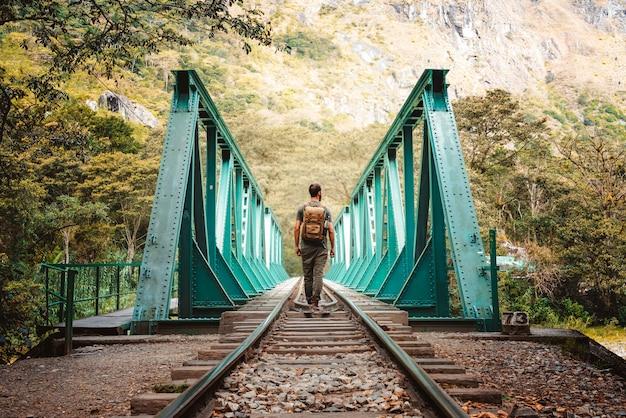 Homme avec sac à dos marchant sur un pont vers la ville de machu picchu