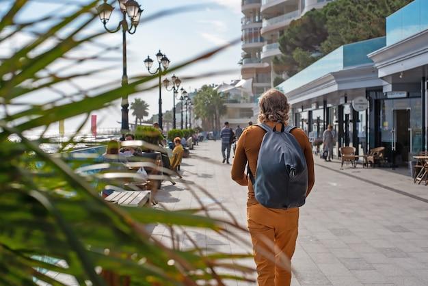 Un homme avec un sac à dos marche le long du remblai